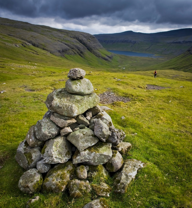 Hiker makes his way down a green valley, with cairn in the foreground, Faroe Islands, Scandinavia